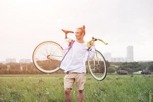 homem sorridente na camiseta em branco andando com bicicleta