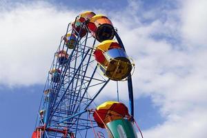 roda gigante colorida com céu azul nublado no fundo foto