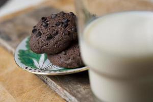 biscoitos de chocolate e copo de leite na chapa de madeira foto