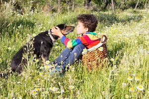garoto bonito está beijando seu cachorro