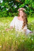 garota com cabelo comprido no campo com margaridas foto
