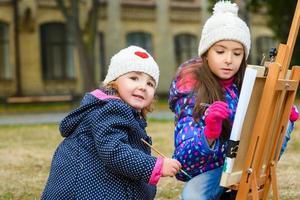 meninas bonitos desenha tintas em um cavalete ao ar livre foto