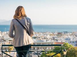 menina sentada num banco acima de uma cidade foto