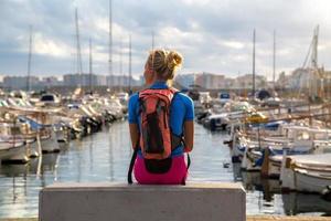 jovem mulher sentada no porto foto
