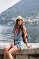 menina sorridente, apreciando a vista para o lago foto