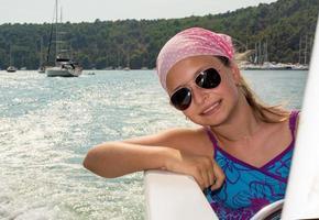 menina, desfrutando de velejar em um barco foto