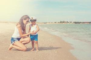 feliz linda mãe e filho, aproveitando o tempo na praia foto