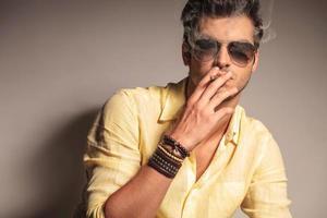 homem legal moda com óculos de sol, desfrutando de seu cigarro