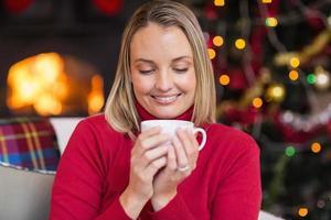 loira bonita, desfrutando de uma bebida quente no Natal foto