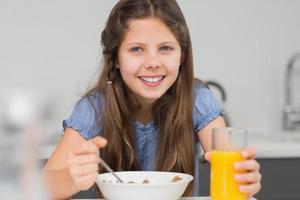 jovem sorridente tomando café da manhã na cozinha foto