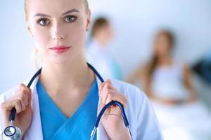 médico de mulher em pé com estetoscópio no hospital foto