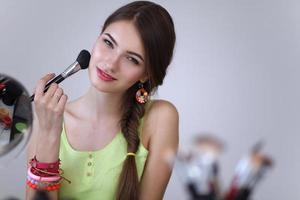jovem mulher bonita fazendo maquiagem perto de espelho foto