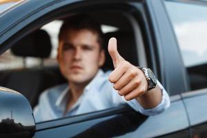 homem bonito, sentado em um carro e segurando os polegares