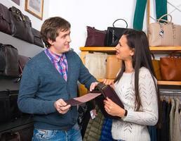 assistente de loja, mostrando a bolsa de couro para mulher bonita foto