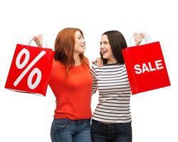 dois sorrindo adolescente com sacos de compras foto