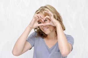 mulher jovem sorridente fazendo coração com os dedos foto