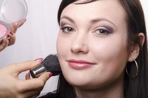 maquiador lida com pó no modelo de rosto foto