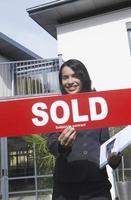 agente imobiliário segurando vendido sinal fora de casa foto