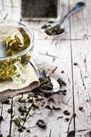 xícara de chá verde e colheres foto