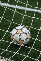 vista de uma bola de futebol dentro da trave foto