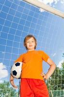 retrato de menino de uniforme com futebol