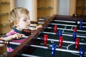 menino loiro jogando futebol de mesa mesa em casa. foto