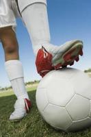 jogador de futebol com perna na bola