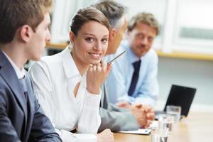 mulher sorridente, sentado em uma reunião de negócios com colegas foto