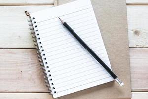 caderno e lápis na mesa de madeira foto