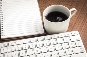 caderno vazio, teclado e café na mesa de madeira foto