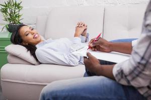 mulher deitada no sofá enquanto psicólogo escrevendo foto