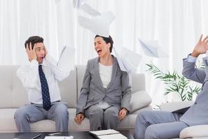 empresários chocados com colega gritando e jogando papéis foto
