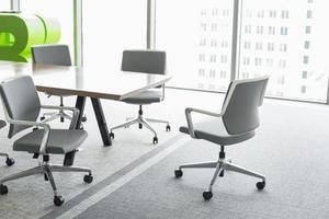 cadeiras de escritório na mesa de conferência foto