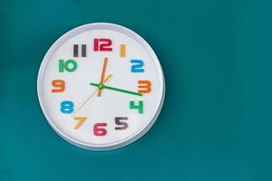 relógio branco na parede verde foto