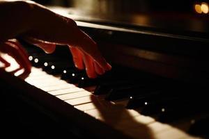 mãos tocando piano com pouca luz foto