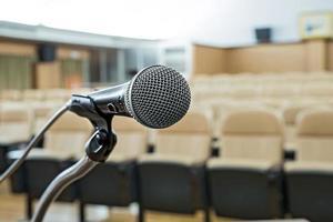 antes de uma conferência, os microfones na frente de cadeiras vazias. foto