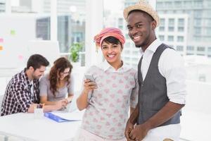 colegas de trabalho sorridentes com o telefone móvel em pé foto