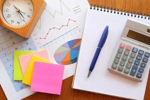 caderno e gráfico na mesa de madeira com calculadora foto