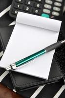 caneta no bloco de notas foto