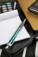 caneta colocar no bloco de notas em branco foto