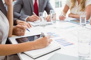 seção intermediária de executivos escrevendo notas em reunião na sala de diretoria foto