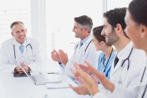 médicos aplaudindo um colega médico foto