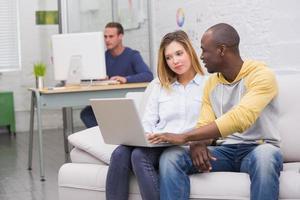colegas casuais usando laptop no sofá no escritório foto
