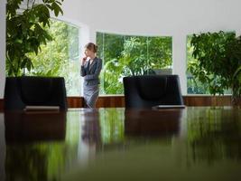 empresária, contemplando fora da janela na sala de reuniões foto