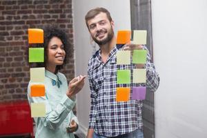 equipe de negócios olhando notas auto-adesivas na janela foto