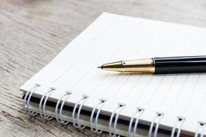 caneta no caderno em branco foto