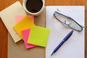 caderno na mesa de madeira com café foto
