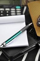caneta e papel em branco no caderno preto foto