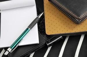 caneta e bloco de notas com fundo de livro de nota foto