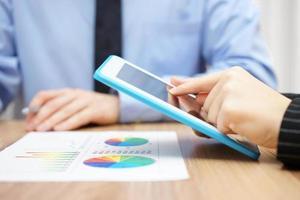 empresário e empresária trabalhando com tablet e relatório de papel